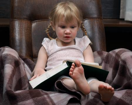 65750634-little-girl-with-a-large-book-green-book-the-girl-in-the-chair-a-girl-with-two-braids-wearing-a-whit